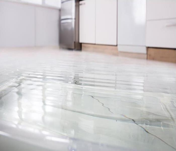 Kitchen tile floor covered in a layer of water