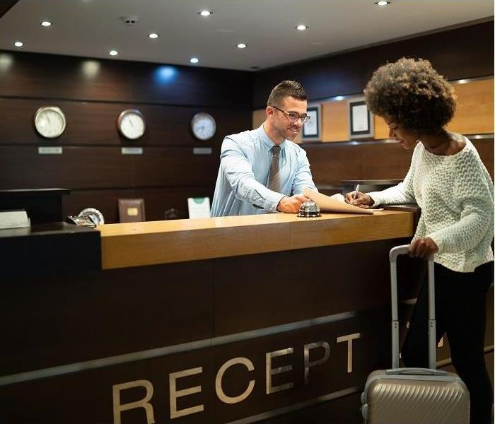 Hotel clerk helping guest check into hotel