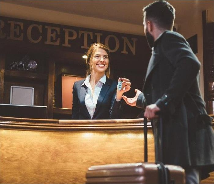 Receptionist giving keys to hotel guest