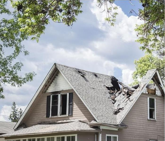 Fire damage on roof and attic of two-story home