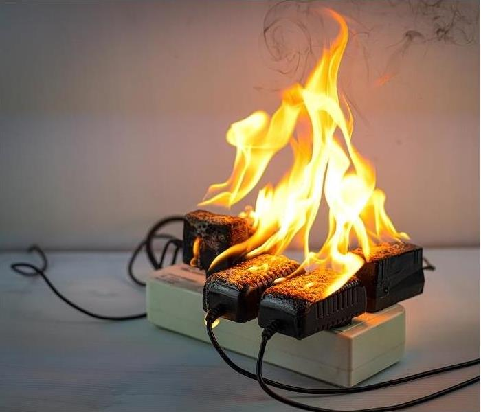 Overloaded power strip; cords catching fire and beginning to burn