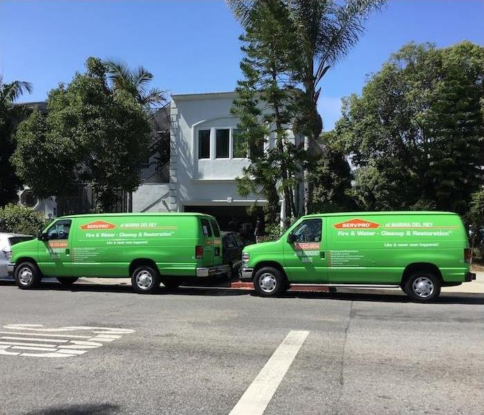 2 green SERVPRO vans parked on the street in front of a blue house